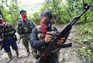 Integrantes da frente Che Guevara do Exército de Libertação Nacional limpam suas armas na selva, no departamento colombiano de Choco Foto: RAUL ARBOLEDA / Agência O Globo / 25-05-2019