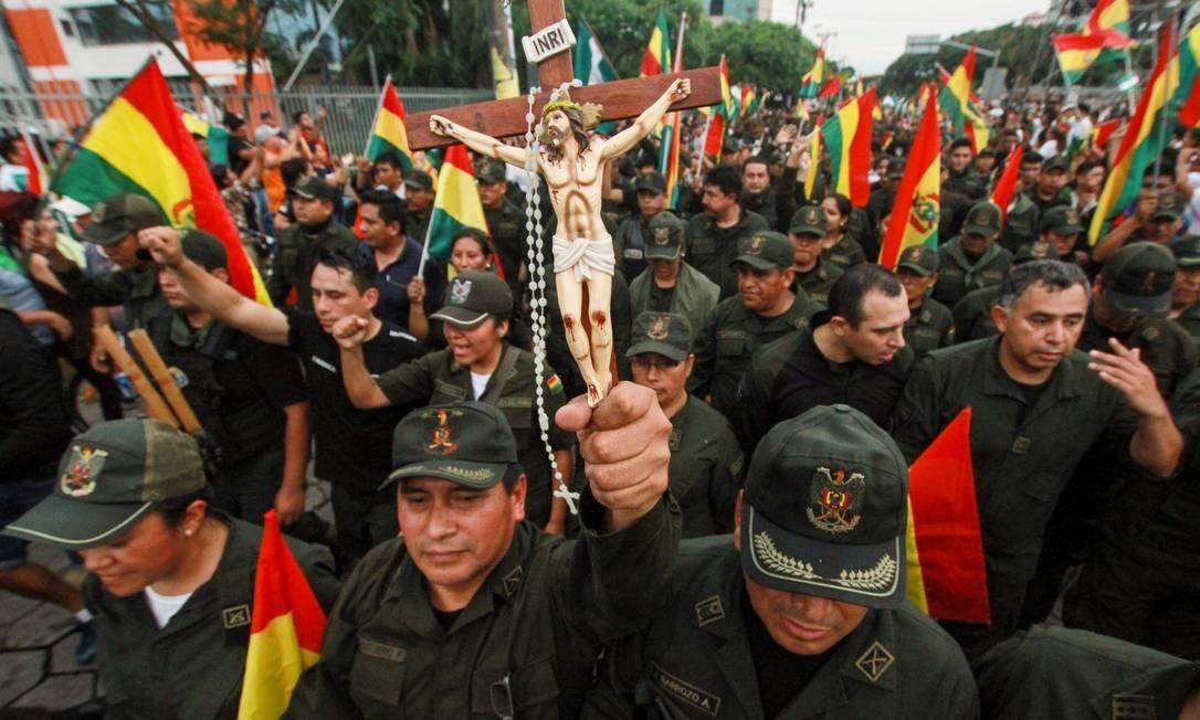 Oficial da polícia carrega crucifixo em desfile em comemoração à renúncia do presidente, em Santa Cruz de La Sierra, reduto oposicionista Foto: Daniel Walker / AFP