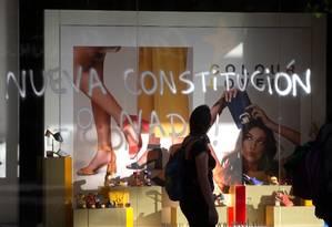 """Mulher olha para pichação """"Nova Constituinção ou nada!"""" em vidro de loja em Santiago, após manifestação contra políticas econômicas do governo Foto: CLAUDIO REYES / AFP/06-11-2019"""