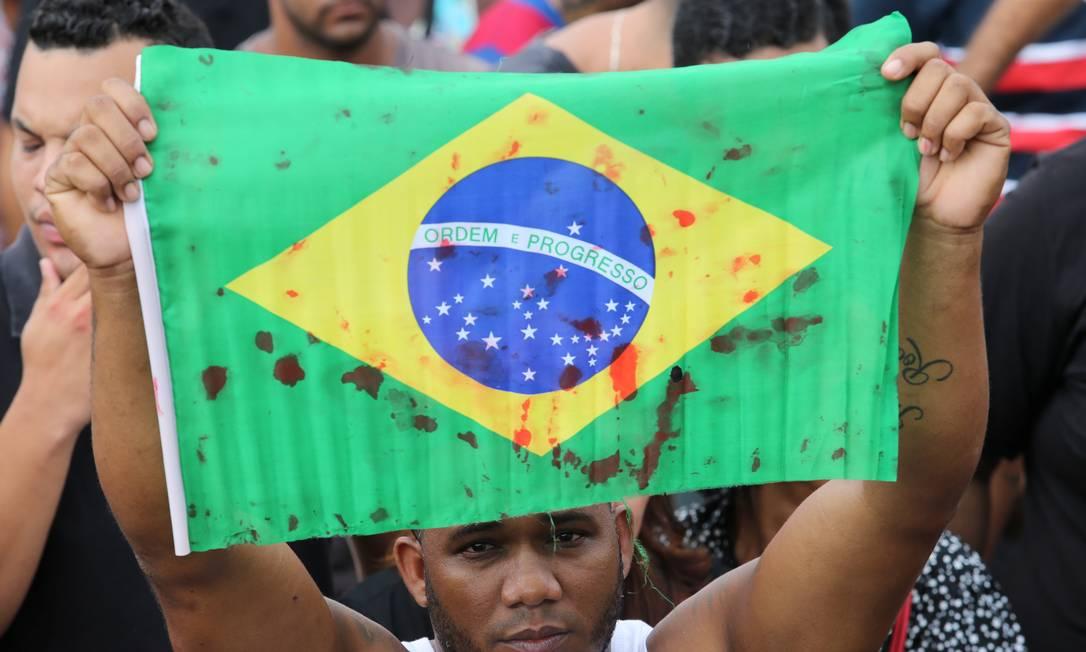 Protesto com bandeiras do Brasil ensanguentadas no enterro de Evaldo dos Santos Rosa, que teve o carro fuzilado com 257 tiros de militares no Rio, no cemitério de Ricardo de Albuquerque Foto: Guilherme Pinto / Agência O Globo