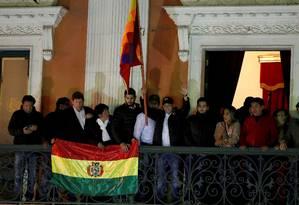 Camacho (segurando uma bandeira indígena) discursa no balcão do palácio presidencial na noite de terça, antes de viajar para a comemoração em Santa Cruz Foto: CARLOS GARCIA RAWLINS / REUTERS