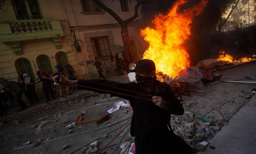 Manifestantes entram em confronto com a polícia nas ruas de Santiago durante o dia de greve geral no país. Governo cogitou adotar estado de emergência, mas desistiu temendo prejudicar o diálogo com a oposição Foto: CLAUDIO REYES / AFP