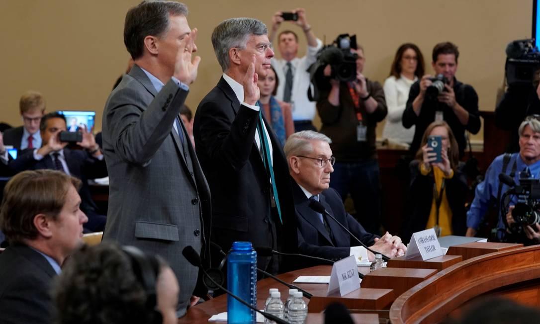 George Kent (E, em pé) e William Taylor (D, em pé), diplomatas relacionados à política americana para a Ucrânia, prestam juramento antes de audiência aberta no processo de impeachment de Donald Trump, na Câmara dos Deputados Foto: JOSHUA ROBERTS / REUTERS