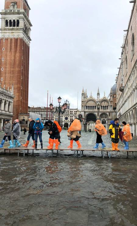 Turistas andam em uma ponte improvisada em rua inundada em Veneza, Itália Foto: Aquaapartaments / Instragram