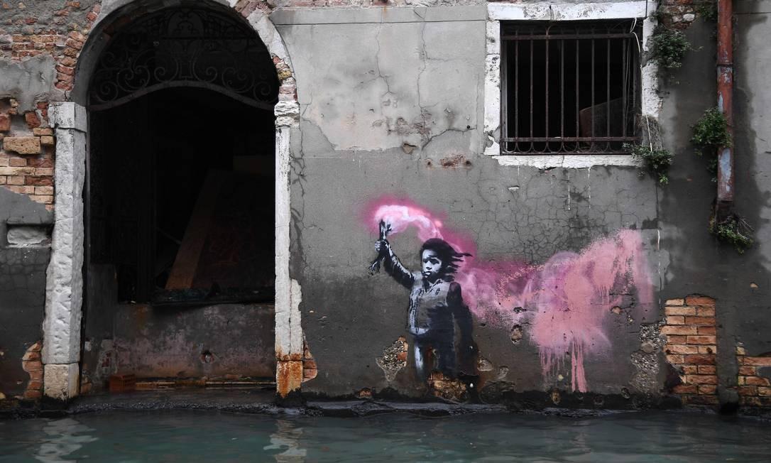 A obra de arte do artista de rua Banksyretrata uma criança imigrante vestindo um colete salva-vidas e segurando sinalizador rosa clicada durante enchente Foto: Marco Bertorello / AFP