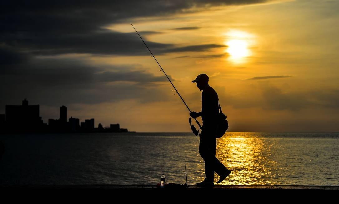 O pescador Roberto Molina, de 69 anos, caminha na Malecón – esplanada ao longo da orla. Molina passou quase metade da vida pescando na mureta que separa Havana do oceano Foto: Yamil Lage / AFP