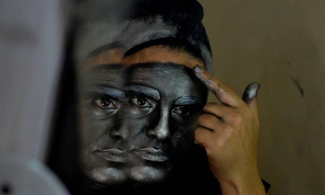 Performando como estátua humana pelo casco turístico de Havana, ela consegue ganhar em um dia o que seu pai, engenheiro naval do governo, ganha me um mês Foto: Yamil Lage / AFP