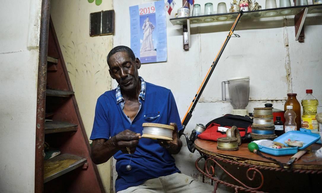Pescar é um ritual. Quase todos os dias Roberto arruma o simplório equipamento. Ele costuma dizer que o diferencial é a habilidade adquirida com o tempo Foto: Yamil Lage / AFP