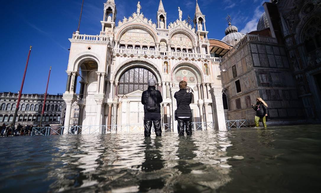 Turistas em ponto inundado da Praça de São Marcos, em Veneza Foto: FILIPPO MONTEFORTE / AFP