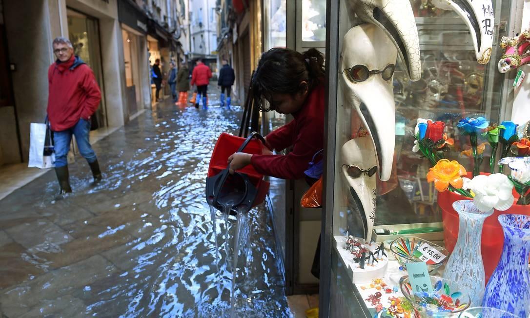 Mulher tira água de uma loja de rua em Veneza Foto: FLAVIO LO SCALZO / REUTERS