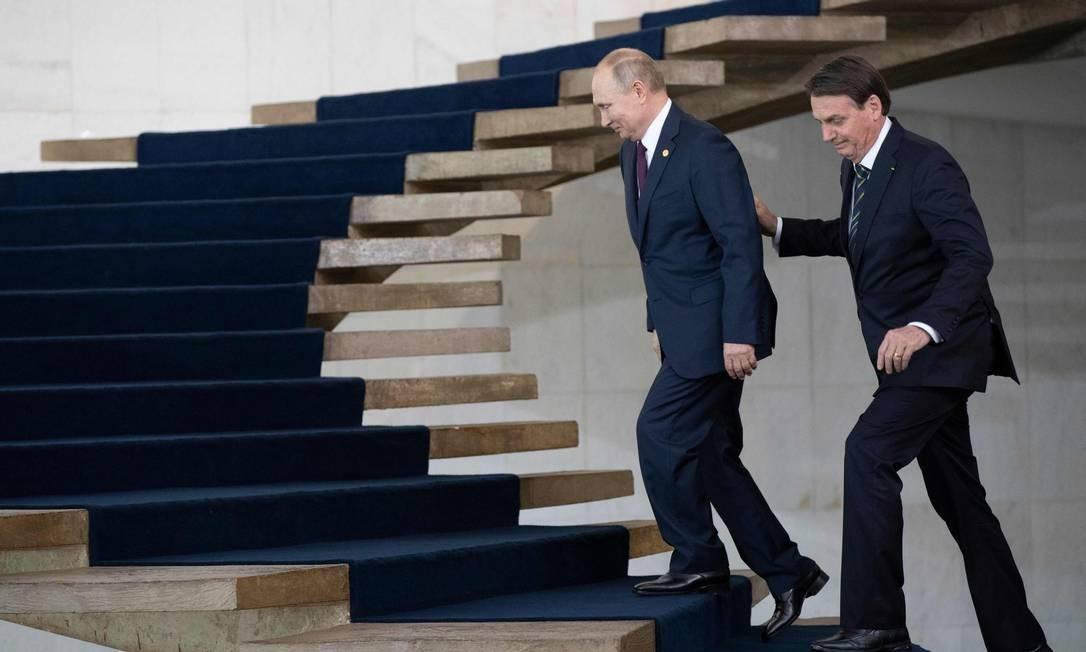 Presidentes da Rússia, Vladimir Putin, e do Brasil, Jair Bolsonaro, sobem escada no Palácio do Itamaraty, às margens da reunião de cúpula do Brics Foto: PAVEL GOLOVKIN / AFP