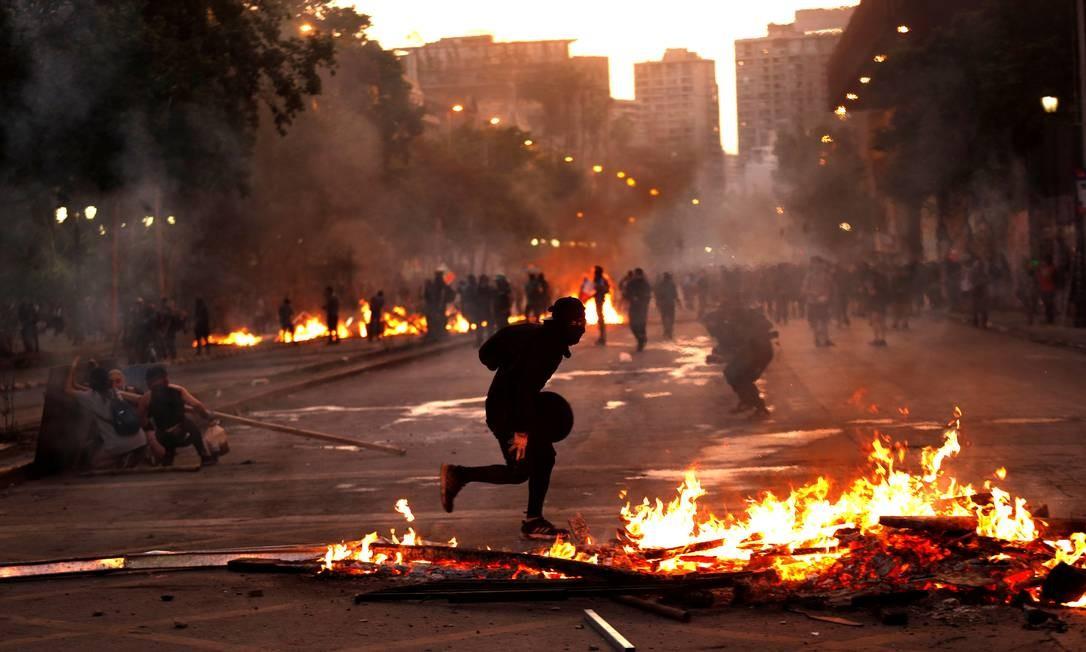 Manifestante mascarado ateia fogo em barricada em protestos contra governo do Chile em Santiago. Foto: JORGE SILVA / REUTERS