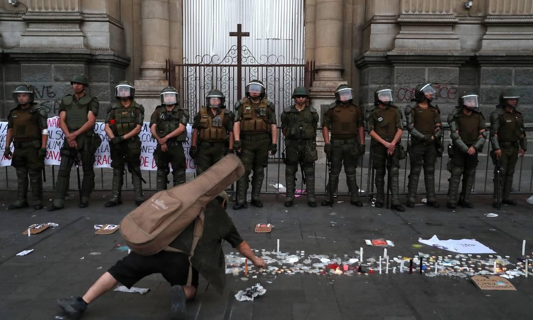 Manifestante coloca velas diante de uma igreja durante novo protesto na capital chilena. Congresso acertou regras para plebiscito que definirá processo para nova Constituição Foto: IVAN ALVARADO / REUTERS