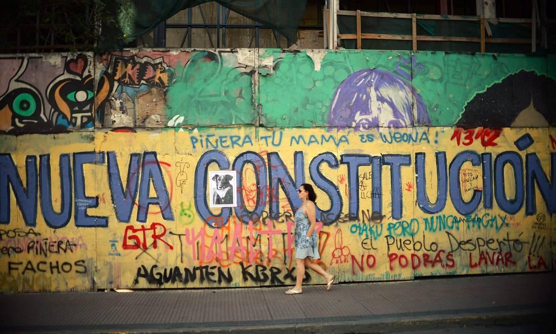 Mulher passa diante de muro pedindo nova constituição em Santiago. Nova Carta, substituindo o texto de 1980, é demanda frequente nos protestos Foto: RODRIGO ARANGUA / AFP