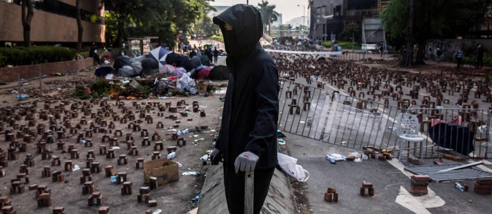 Manifestante em uma rua repleta de tijolos e destroços para impedir o acesso à Universidade Politécnica de Hong Kong: ocupados por ativistas, campi da cidade estão sem aula Foto: ISAAC LAWRENCE / AFP