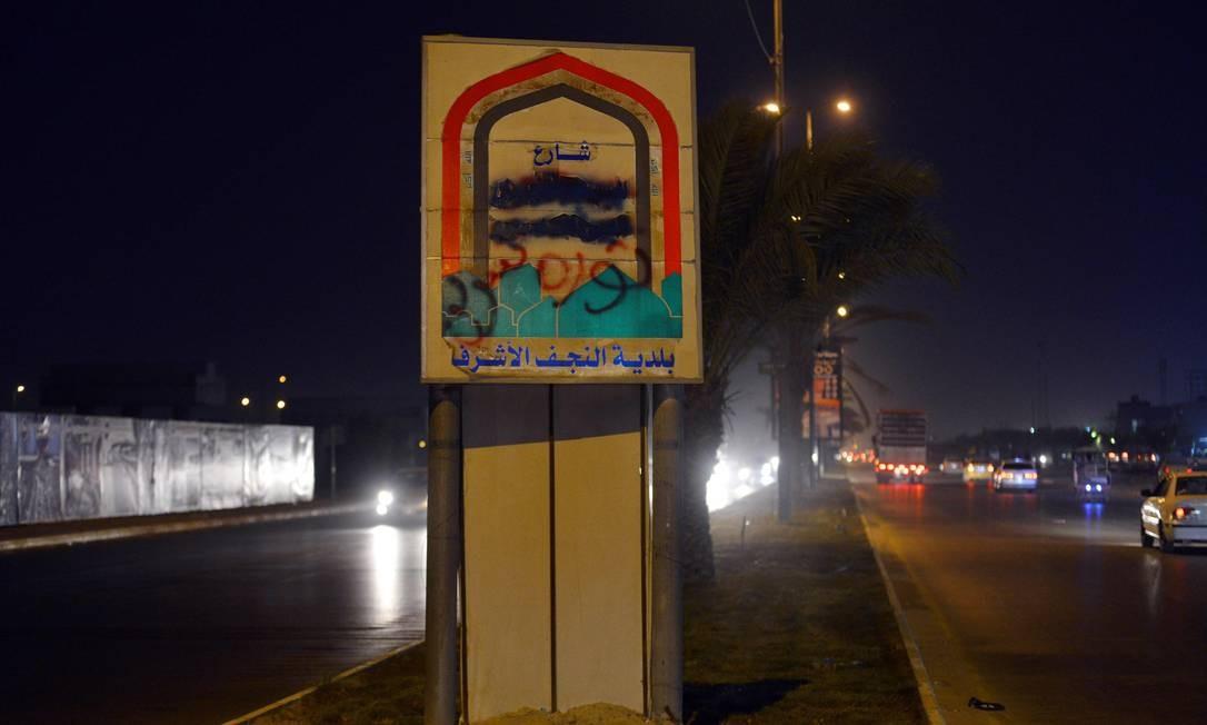 Placa com nome da rua Khomeini, em Najaf, é pichada durante protestos contra o governo. Manifestantes 'trocaram' o nome da rua para 'Revolução' Foto: - / AFP