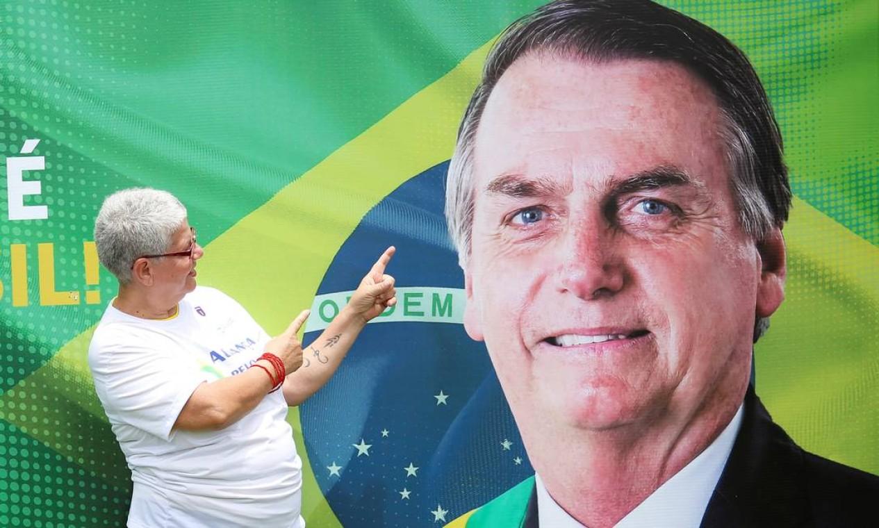 Uma apoiadora posa diante de um painel com a foto de Bolsonaro, que será presidente da nova legenda, lançada nesta quinta-feira, em Brasília Foto: UESLEI MARCELINO / REUTERS