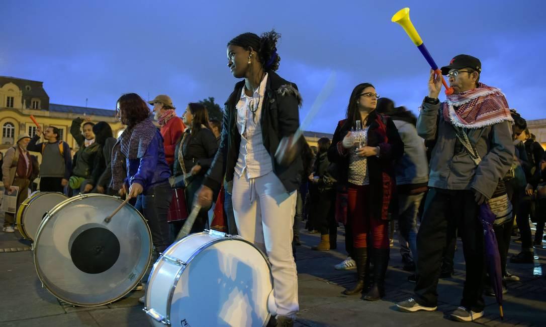 Manifestantes fazem panelaço do lado de fora do Congresso colombiano após um dia de protestos Foto: RAUL ARBOLEDA / AFP