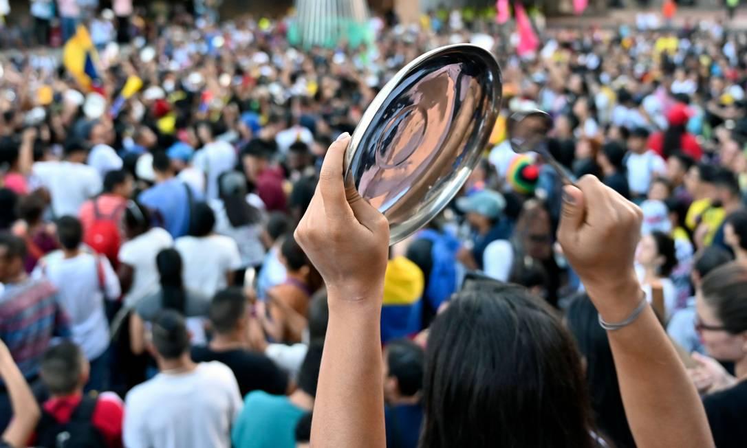 Manifestantes usam panelas durante protesto contra as políticas do governo do presidente da Colômbia, Iván Duque, em Bogotá. Toque de recolher foi decretado nesta sexta-feira na cidade Foto: LUIS ROBAYO / AFP