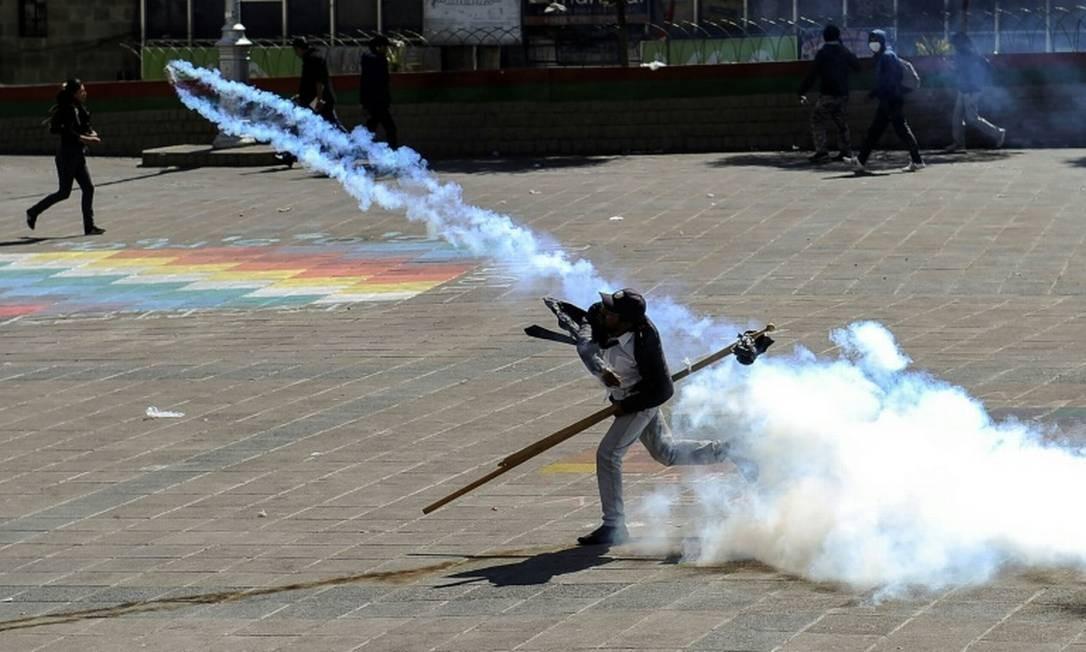 Homem joga lata de gás contra as forças de ordem Foto: AFP / JORGE BERNAL