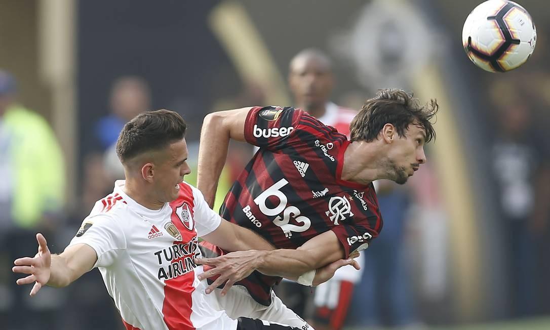 Rodrigo Caio cabeceia em disputa de bola com Borré Foto: LUKA GONZALES / AFP