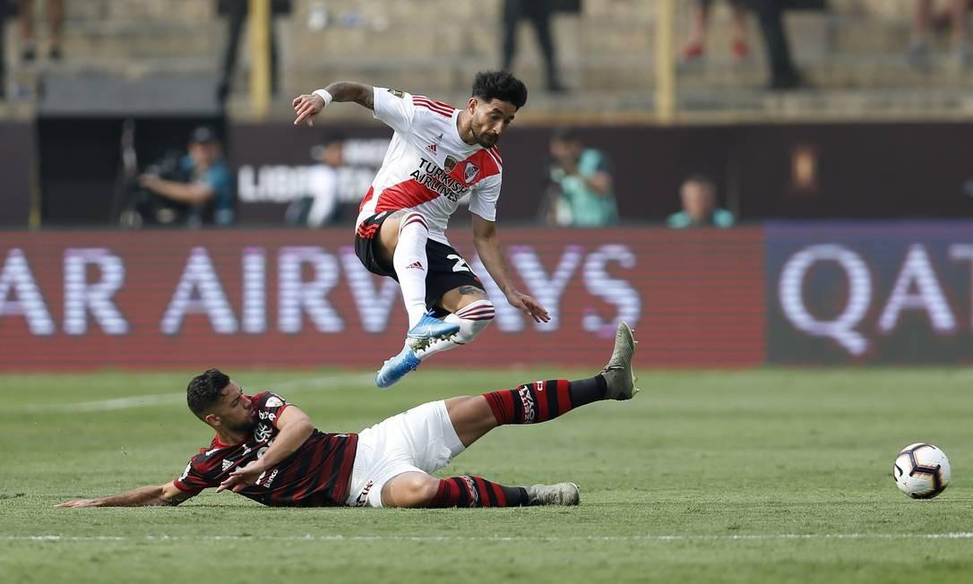 Pablo Marí aplica um carrinho na briga pela bola com Casco Foto: LUKA GONZALES / AFP