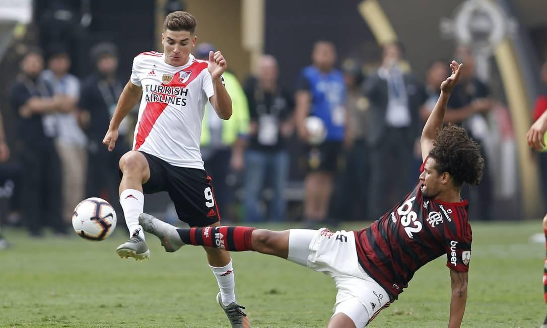 Willian Arão biga pela bola enquanto Alvarez arranca Foto: LUKA GONZALES / AFP