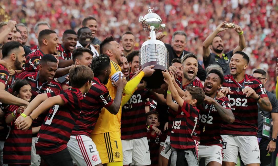 O goleiro Diego Alves e Diego levantam o troféu com os companheiros de equipe Foto: GUADALUPE PARDO / REUTERS