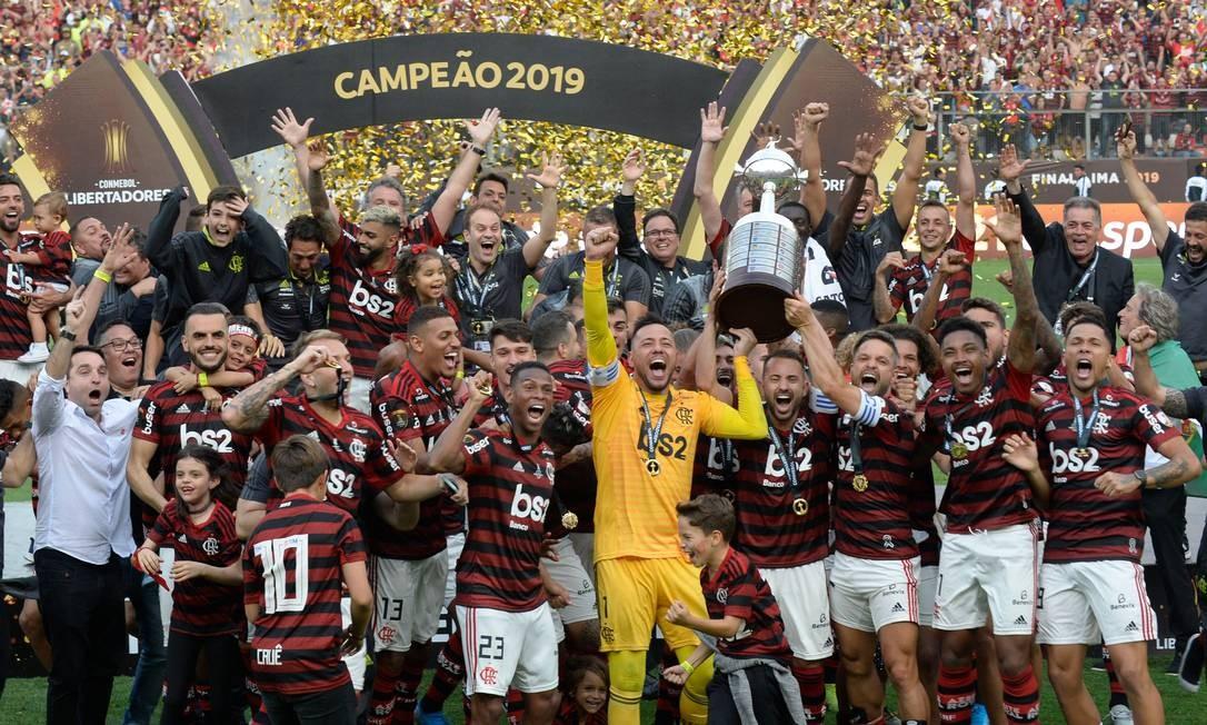 Jogadores do Flamengo do Brasil comemoram no pódio com o troféu depois de vencer a final da Copa Libertadores Foto: ERNESTO BENAVIDES / AFP