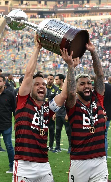 Éverton Ribeiro e Gabriel comemoram erguendo a taça da Libertadores Foto: CRIS BOURONCLE / AFP