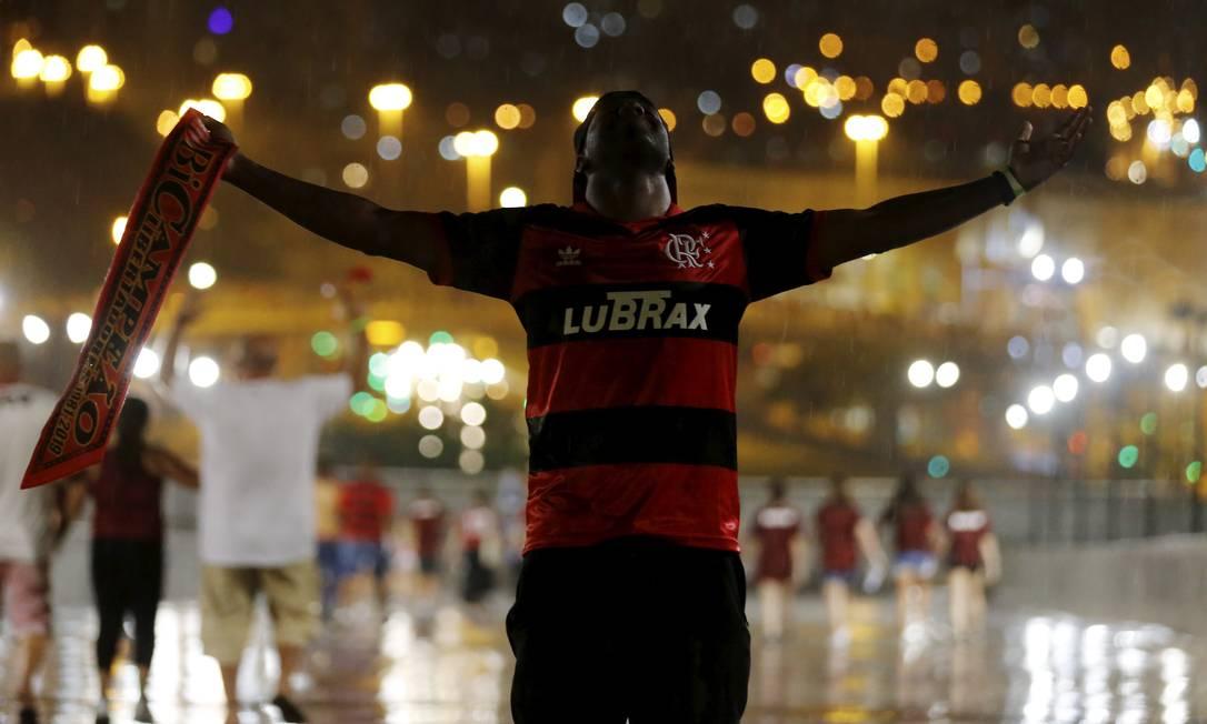 De corpo e alma lavados pela chuva, torcedor do Flamengo comemora título de campeão da América na saída do estádio Maracanã Foto: MARCELO THEOBALD / Agência O Globo