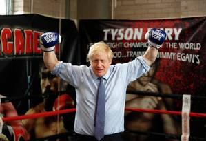 "Primeiro-ministro britânico e líder do Partico Conservador, Boris Johnson veste luvas de boxe com os dizeres ""Get Brexit Done"". Foto: FRANK AUGSTEIN / AFP"