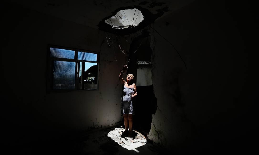 A moradora do Vidigal Dayse Faria dos Santos mostra o buraco que a pedra fez onde era a sua sala Foto: Pablo Jacob / Agência O Globo