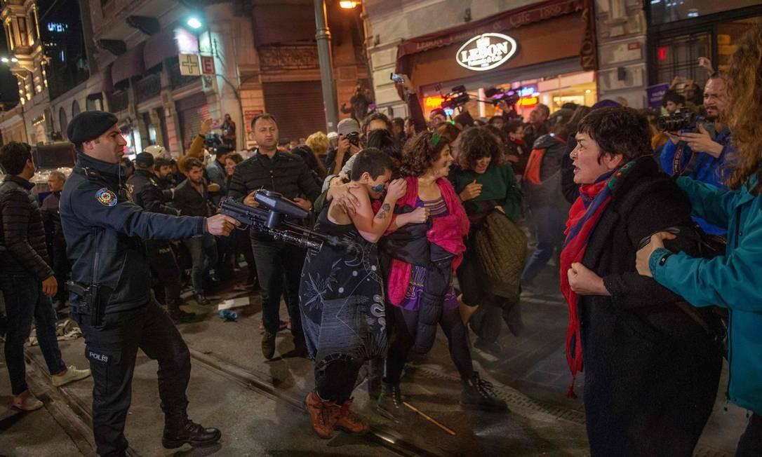Policial turco usa uma arma não letal de mão durante confrontos com ativistas dos direitos das mulheres durante uma marcha em direção à Praça Taksim, em Istambul, na noite de ontem Foto: Bulent Kilic / AFP