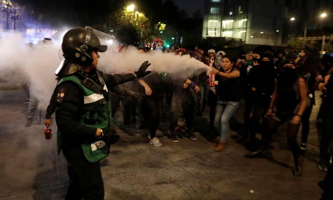 Manifestante dispara extintor de incêndio contra policial em protesto contra o feminicídio e a violência contra as mulheres, na Cidade do México Foto: Luis Cortes / Reuters