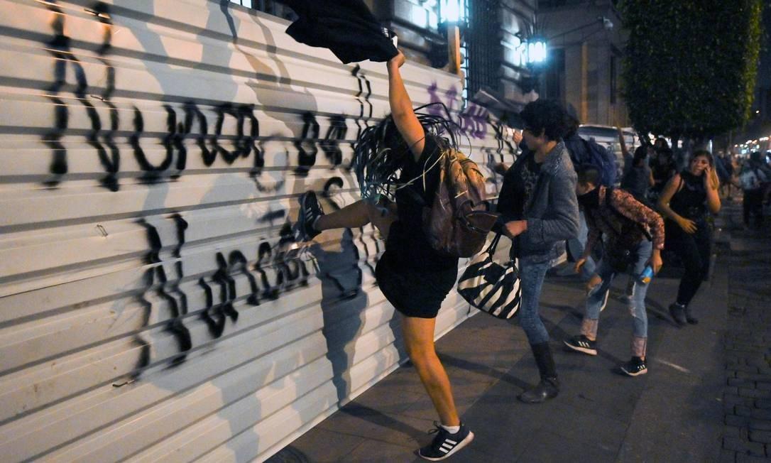 Manifestantes chutam cerca de ferro que isolava prédio histórico no centro da Cidade do México Foto: Pedro Pardo / AFP