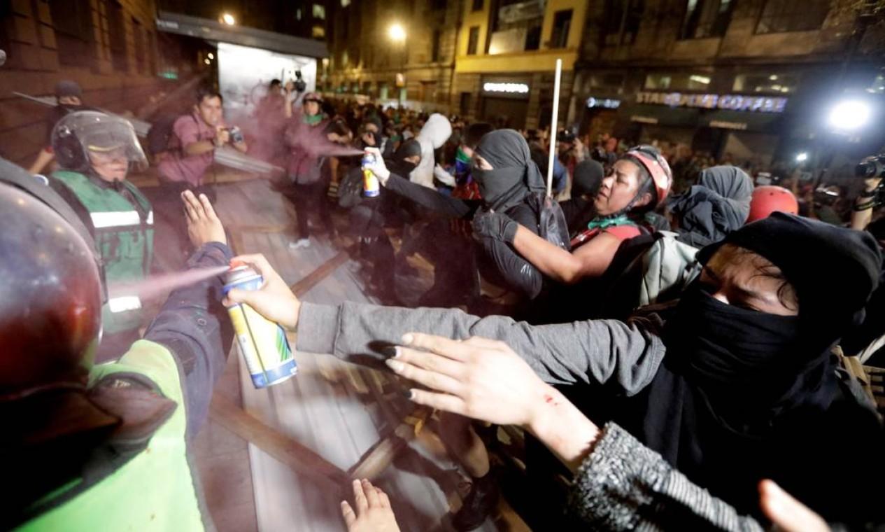 Manifestante dispara spray contra tropa de choque na cidade do México Foto: Luis Cortes / Reuters