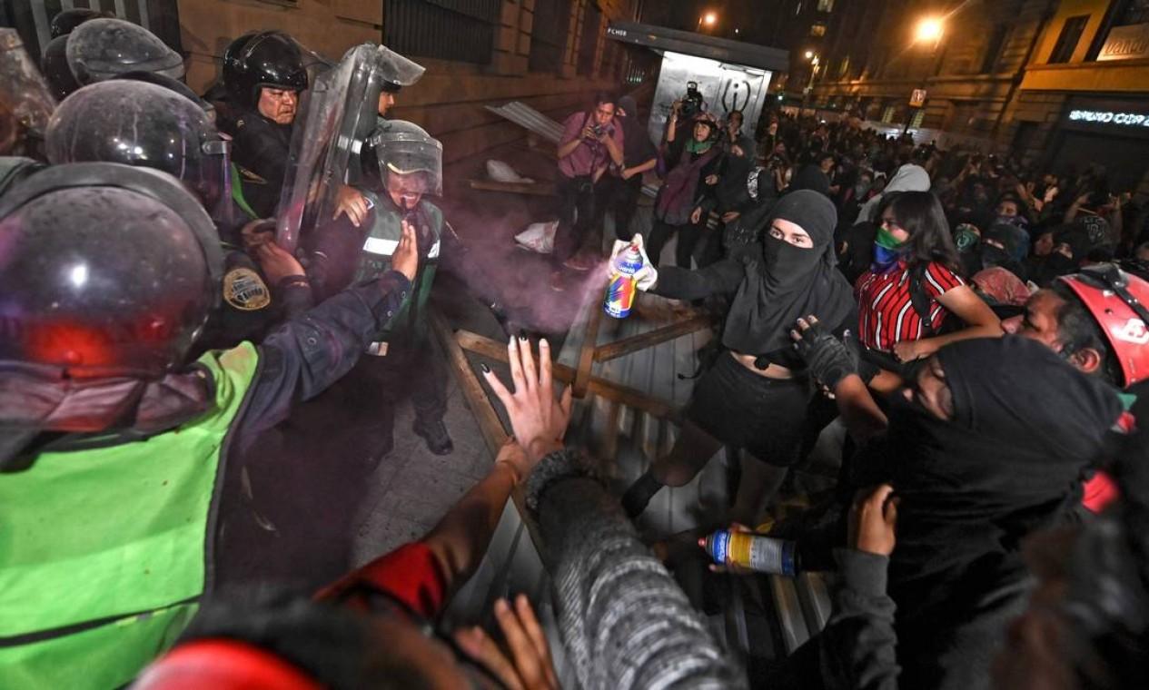 """Manifestante atira spray de tinta rosa na polícia. O gesto é em referência à """"revolução glitter"""", como ficou conhecido o levante das mulheres em agosto, quando o secretário de Segurança da Cidade do México foi pintado de glitter rosa por manifestantes Foto: Pedro Pardo / AFP"""