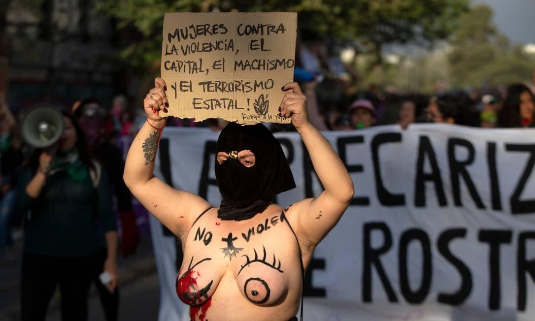 """Chile: """"Mulheres contra a violência, capita, machismo e terrorismo de Estado!"""", diz o cartaz da chilena que também usou o corpo como mensagem: """"sem mais violência"""", diz a frase pintada no colo Foto: Claudio Reyes / AFP"""
