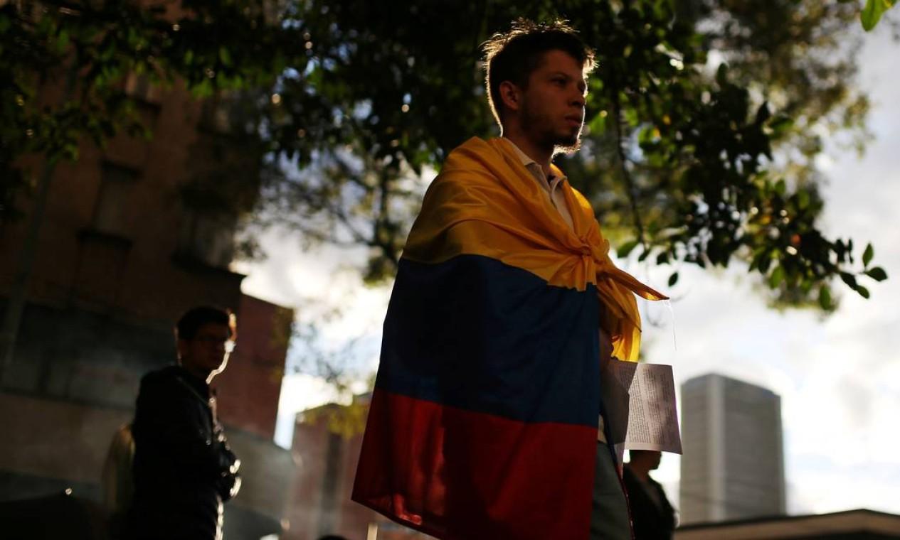 Manifestante se envolve na bandeira nacional colombiana durante uma ato em homenagem a Dilan Cruz Foto: LUISA GONZALEZ / REUTERS