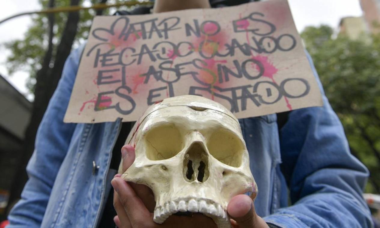 """Estudante segura uma caveira e uma placa com a inscrição """"Matar não é pecado quando o assassino é o Estado"""" durante uma vigília em homenagem a Dilan Cruz Foto: RAUL ARBOLEDA / AFP"""