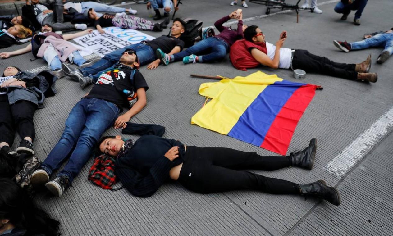 Manifestantes deitam no chão ao lado de uma bandeira colombiana durante um protesto, enquanto uma greve nacional continua em Bogotá Foto: CARLOS JASSO / REUTERS