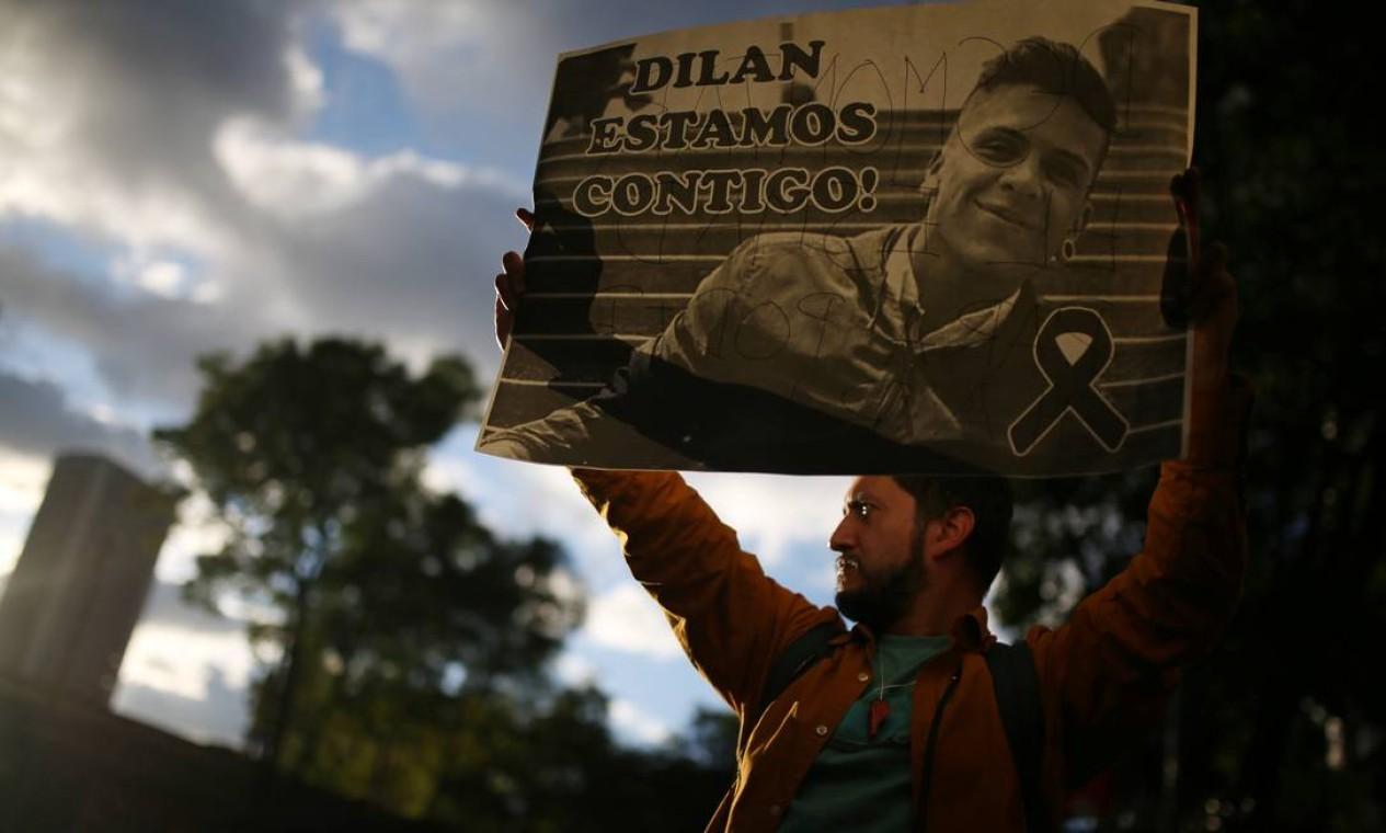 Homem segura cartaz com foto de Dilan Cruz. Adolescente participava de uma passeata no centro de Bogotá, no sábado Foto: LUISA GONZALEZ / REUTERS