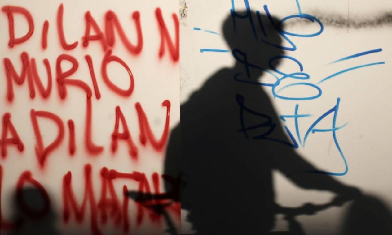 """A sombra de uma pessoa em frente a um grafite que diz: """"Dilan não morreu; Dilan foi morto"""" Foto: LUISA GONZALEZ / REUTERS"""