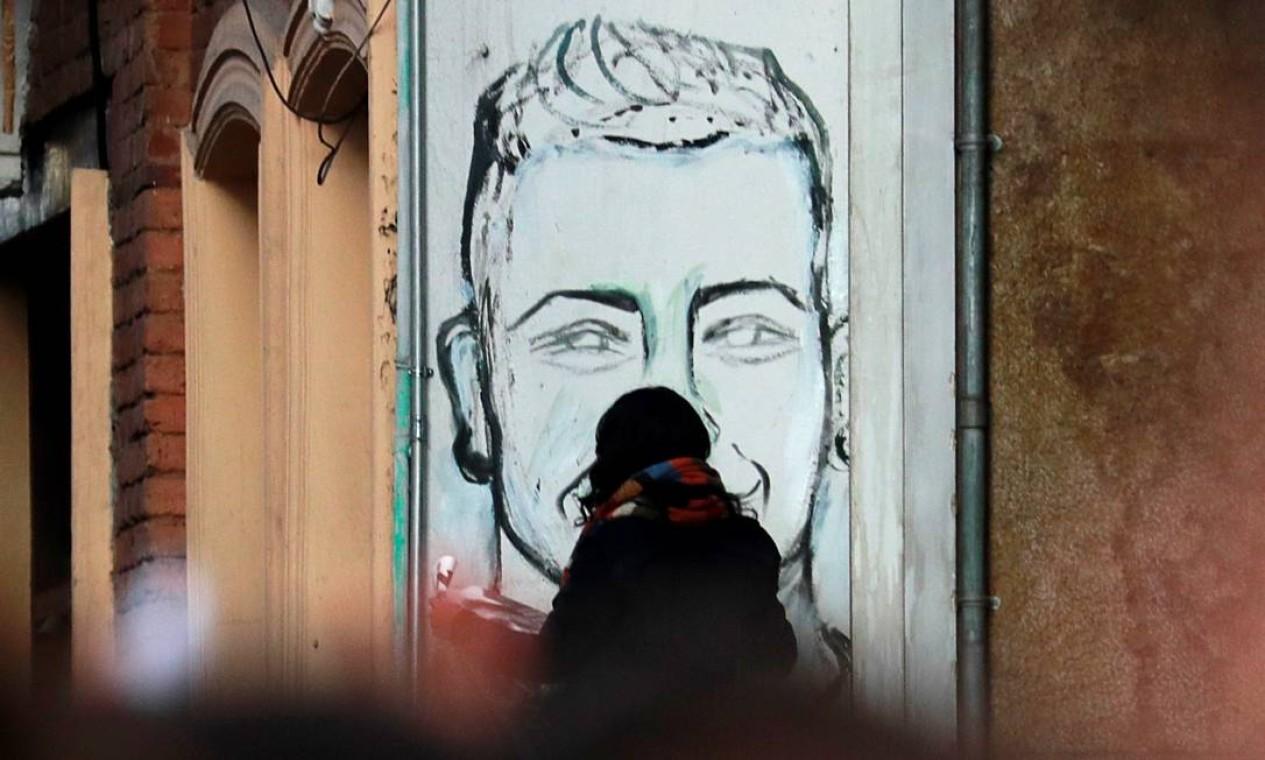 Mulher passa por um grafite representando Dilan Cruz. O jovem de 18 anos se converteu no rosto dos protestos da Colômbia Foto: CARLOS JASSO / REUTERS