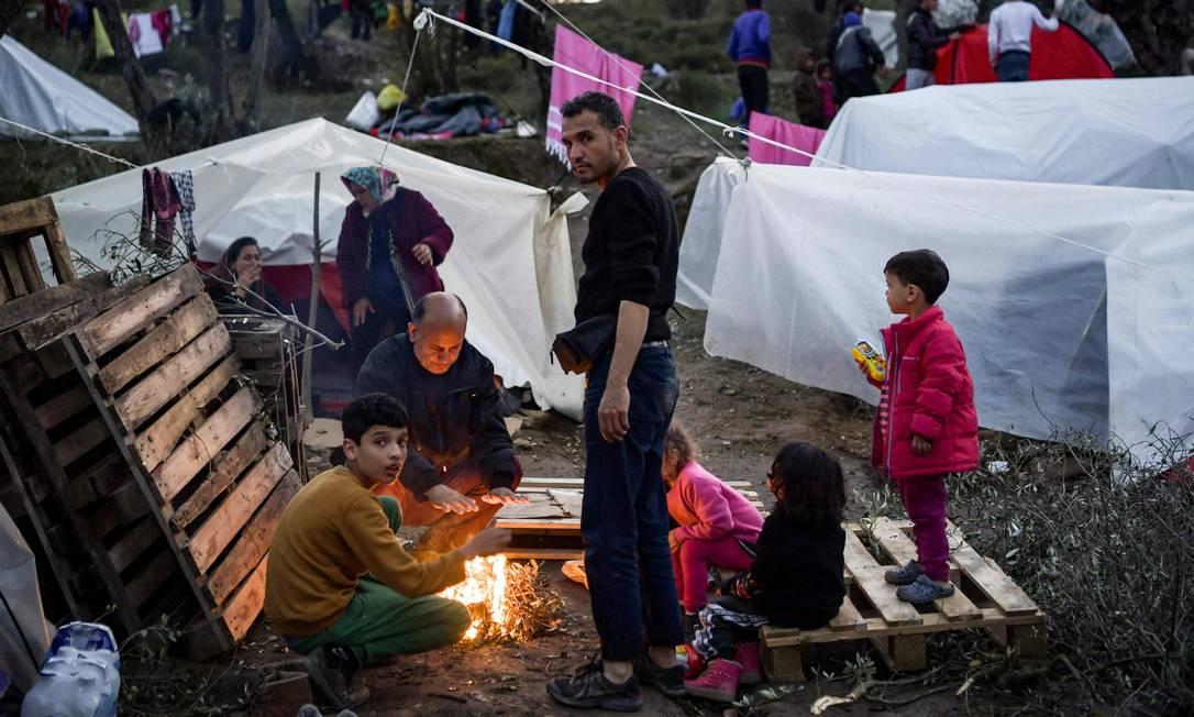 Família em volta de fogueira no acampamento de Moria, na ilha grega de Lesbos Foto: ARIS MESSINIS / AFP