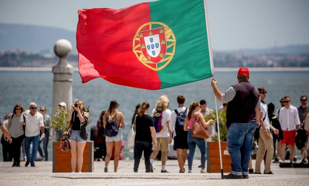 Homem segura bandeira portuguesa enquanto turistas passeiam por Lisboa Foto: MICHAEL KAPPELER / Agência O Globo/31-11-2019