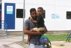 Jeferson de Oliveira Feitosa com o filho Théo: 'Um absurdo ter que ficar andando com essa criança passando mal' Foto: Guilherme Pinto / Agência O Globo