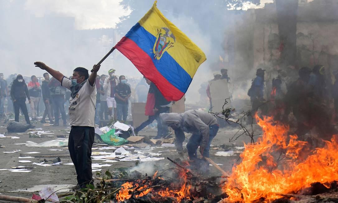 Manifestante ergue a bandeira do Equador em um dos violentos protestos que tomaram o país no início do mês passado depois que o presidente Lenín Moreno lançou pacote de austeridade econômica que eliminou subsídios de décadas aos combustíveis Foto: MARTIN BERNETTI/AFP/12-10-2019