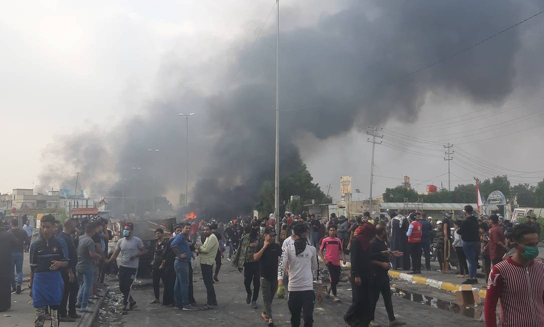Veículos queimados em bloqueio montado por manifestantes nas ruas de Nassíria, em meio a enfrentamentos com as forças de segurança Foto: STRINGER / REUTERS